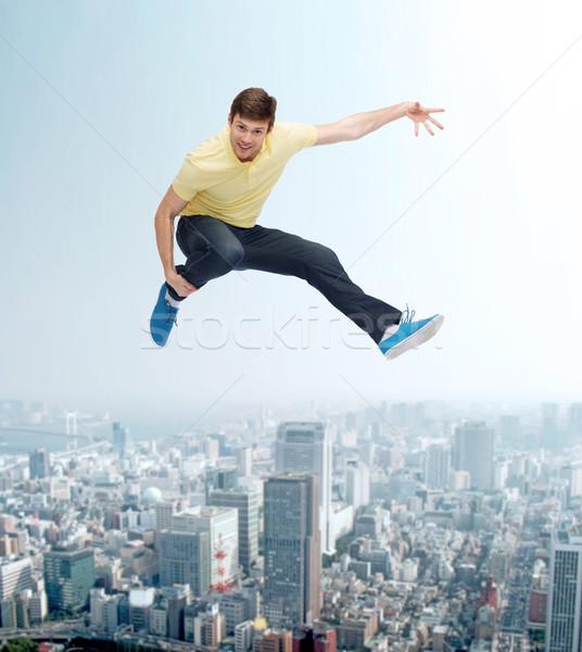 Gülen genç atlama hava mutluluk özgürlük Stok fotoğraf © dolgachov