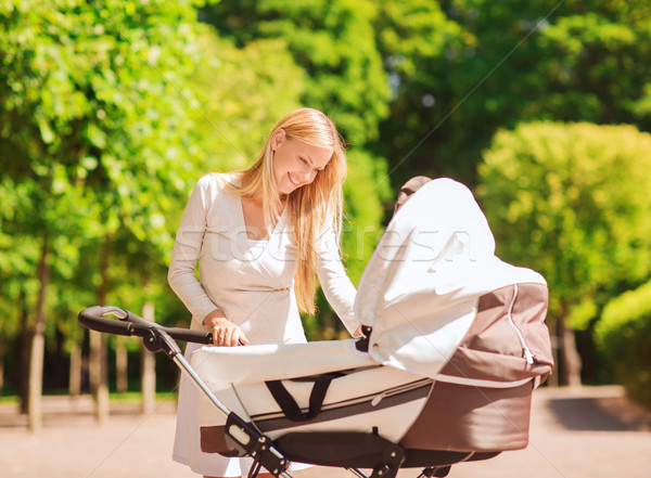 happy mother with stroller in park Stock photo © dolgachov