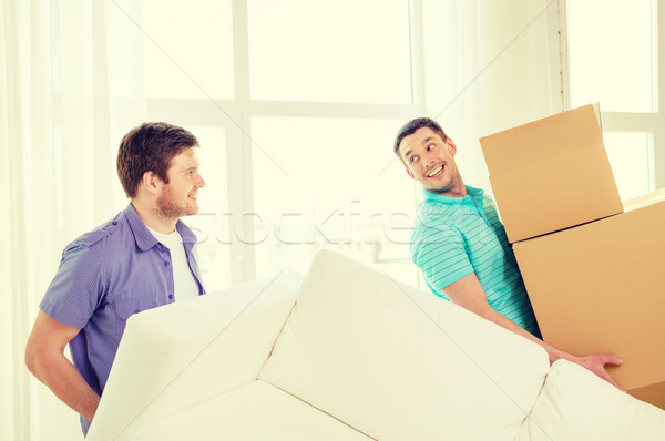 smiling friends with sofa and boxes at new home Stock photo © dolgachov