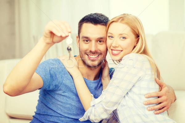 smiling couple holding keys at home Stock photo © dolgachov