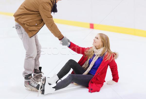 man helping women to rise up on skating rink Stock photo © dolgachov