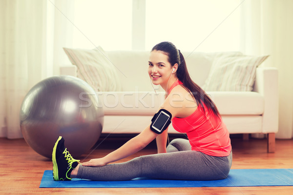 smiling girl with armband execising at home Stock photo © dolgachov