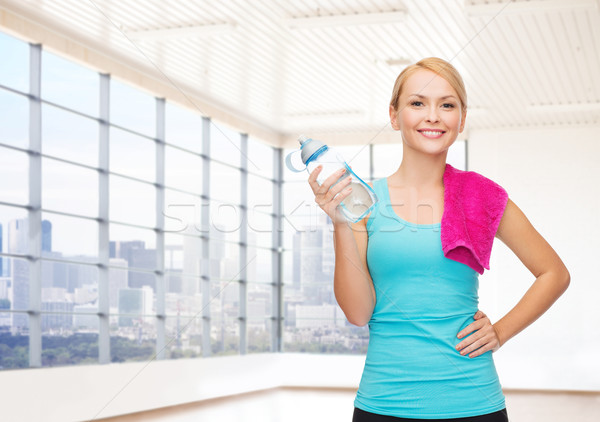 happy woman with bottle of water and towel in gym Stock photo © dolgachov