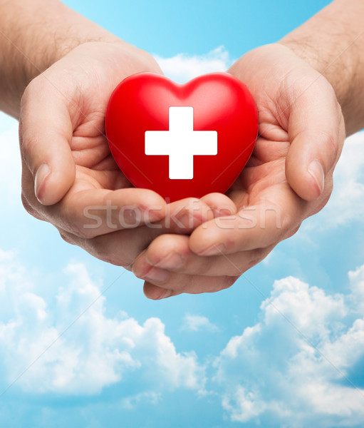 male hands holding red heart with white cross Stock photo © dolgachov