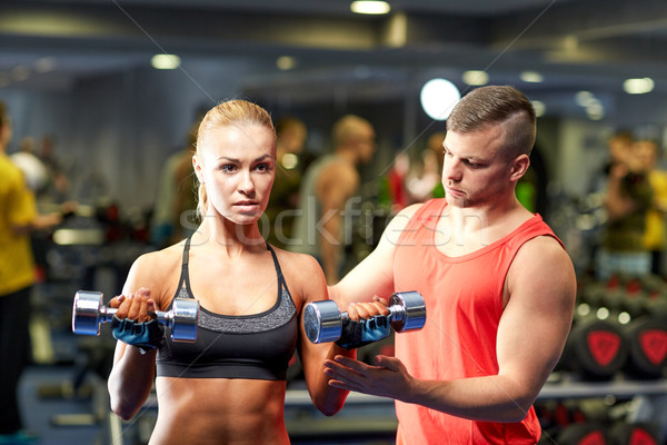 Stock photo: young couple with dumbbells flexing muscles in gym