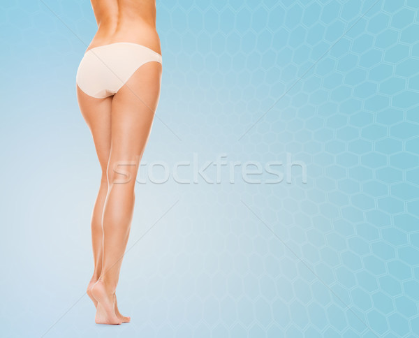 woman long legs in cotton panties over blue Stock photo © dolgachov