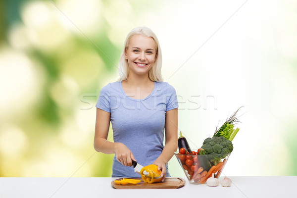 smiling young woman chopping vegetables at home Stock photo © dolgachov