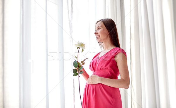 happy pregnant woman with rose flower at home Stock photo © dolgachov