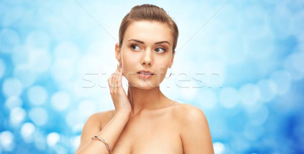 Femme or boucles d'oreilles bracelet lumières beauté Photo stock © dolgachov