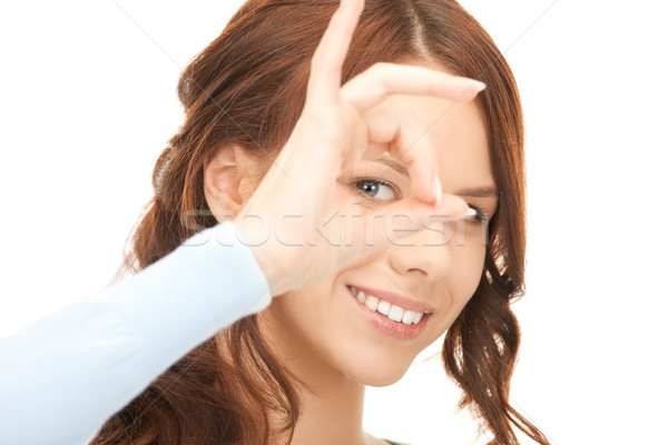 lovely woman looking through hole from fingers Stock photo © dolgachov