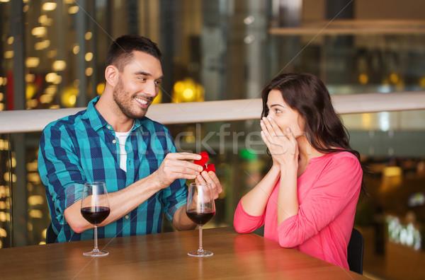 man giving engagement ring to woman at restaurant Stock photo © dolgachov