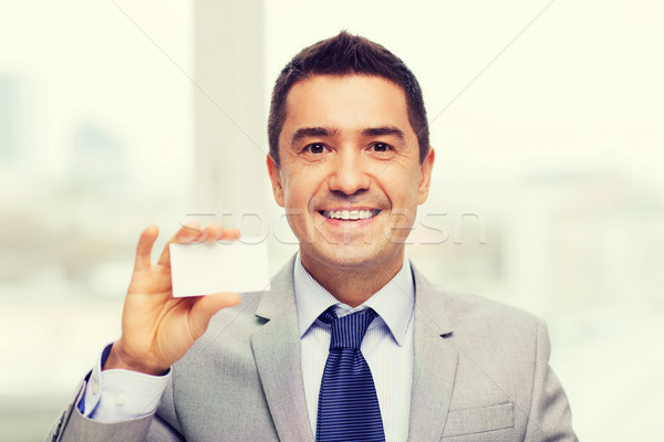 Stock photo: smiling businessman in suit showing visiting card