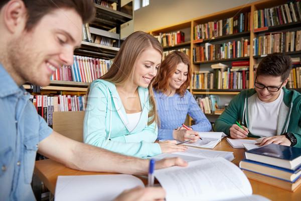 Boldog diákok ír jegyzetfüzetek könyvtár emberek Stock fotó © dolgachov