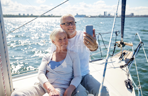 seniors with smartphone taking selfie on yacht Stock photo © dolgachov