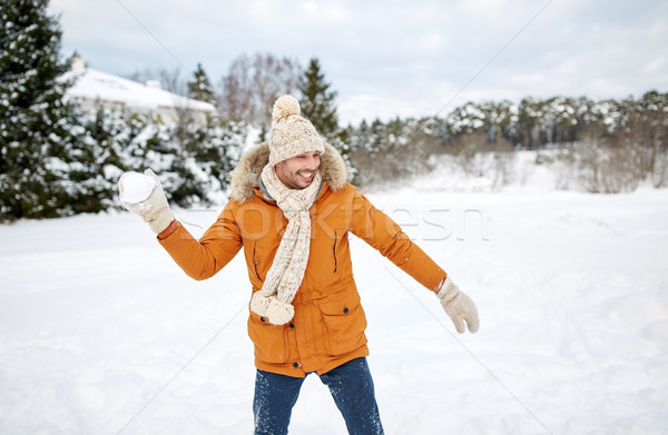 happy young man playing snowballs in winter Stock photo © dolgachov