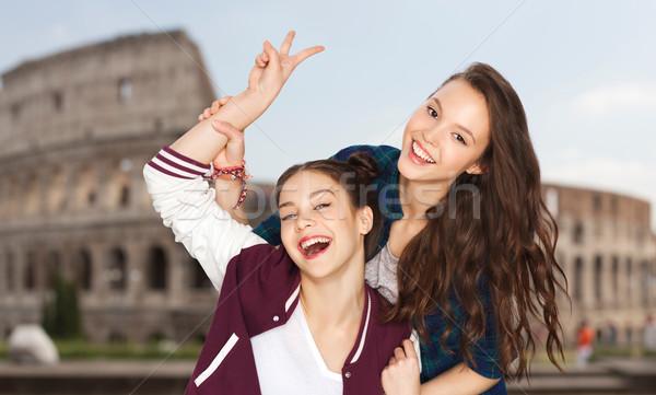 happy teenage girls showing peace over coliseum Stock photo © dolgachov