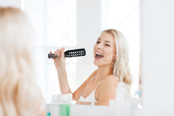 happy woman singing to hair brush at bathroom Stock photo © dolgachov