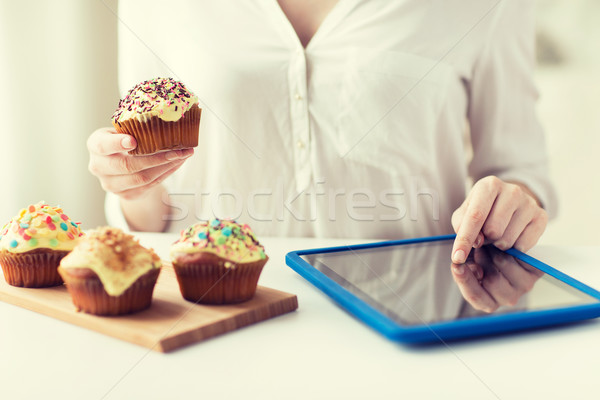 close up of woman with cupcakes and tablet pc Stock photo © dolgachov