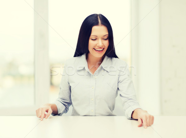 smiling woman pointing to something imaginary Stock photo © dolgachov