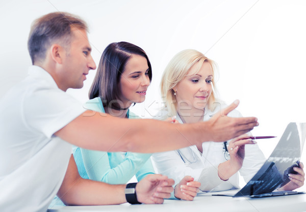 doctor with patients looking at x-ray Stock photo © dolgachov