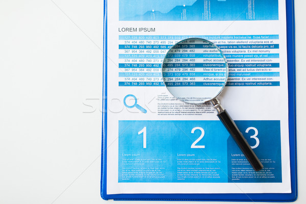 close up of financial report and magnifying glass Stock photo © dolgachov