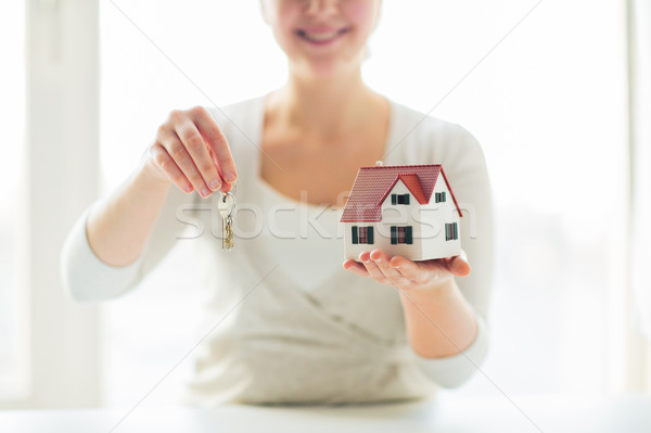 close up of woman holding house model and keys Stock photo © dolgachov