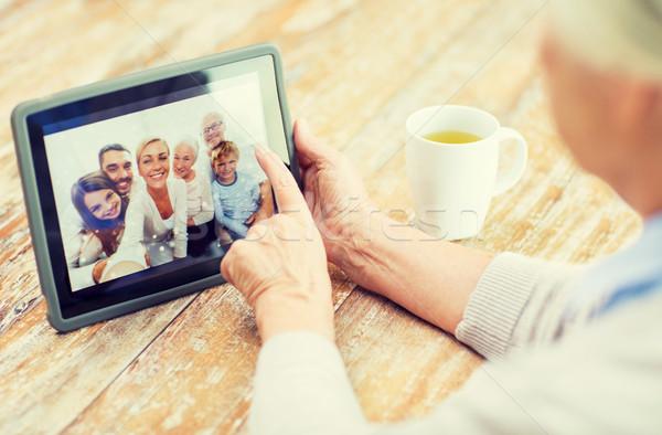senior woman with family photo on tablet pc screen Stock photo © dolgachov