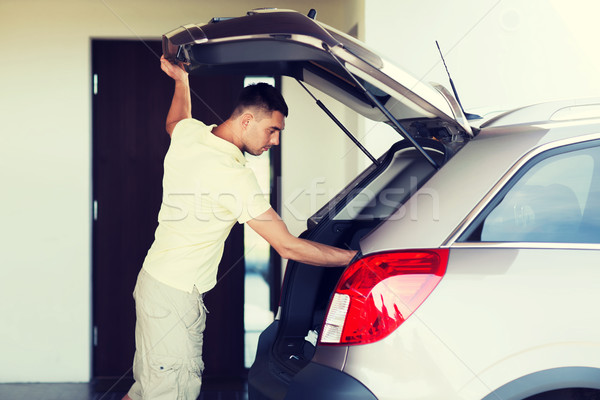 young man with open car trunk at parking space Stock photo © dolgachov