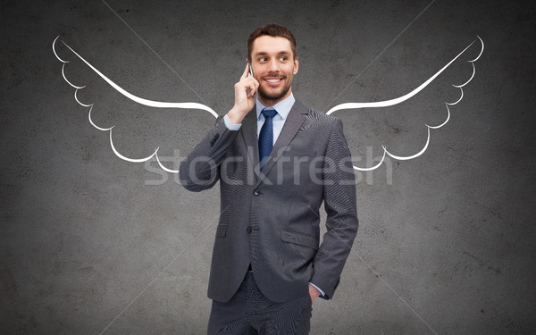 businessman with angel wings calling on cellphone Stock photo © dolgachov