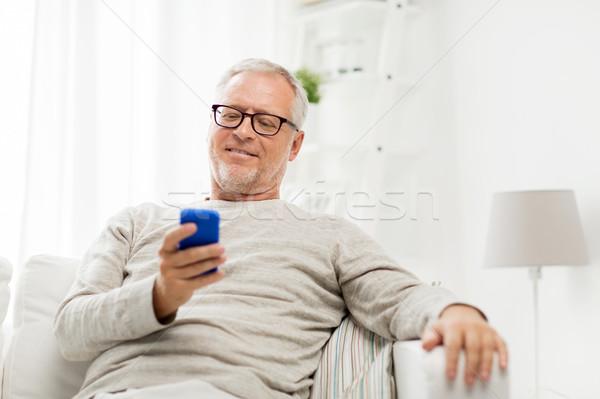 Boldog idős férfi sms chat okostelefon otthon Stock fotó © dolgachov