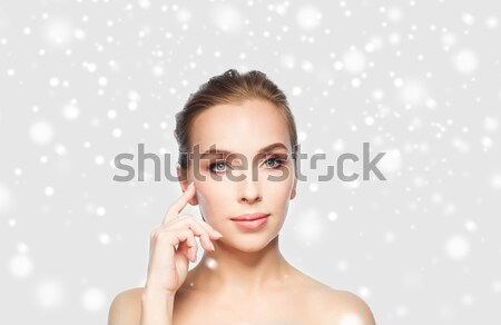 beautiful young woman touching her face over snow Stock photo © dolgachov