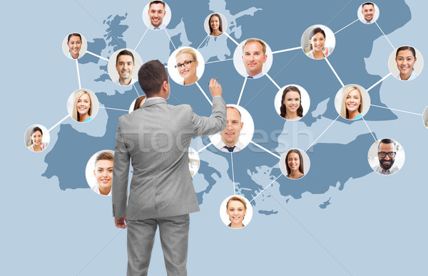 businessman at virtual screen with contacts Stock photo © dolgachov