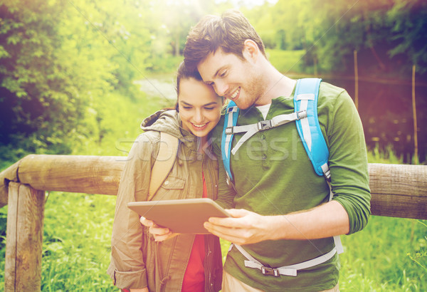 happy couple with backpacks and tablet pc outdoors Stock photo © dolgachov