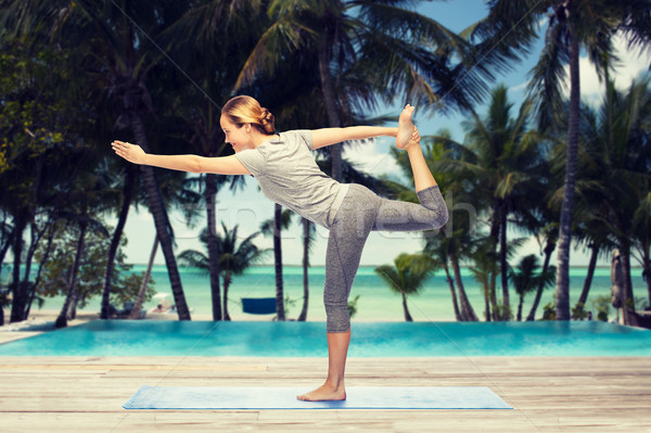 woman making yoga in lord of the dance pose on mat Stock photo © dolgachov