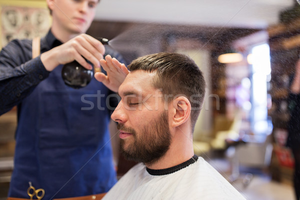 barber applying styling spray to male hair Stock photo © dolgachov