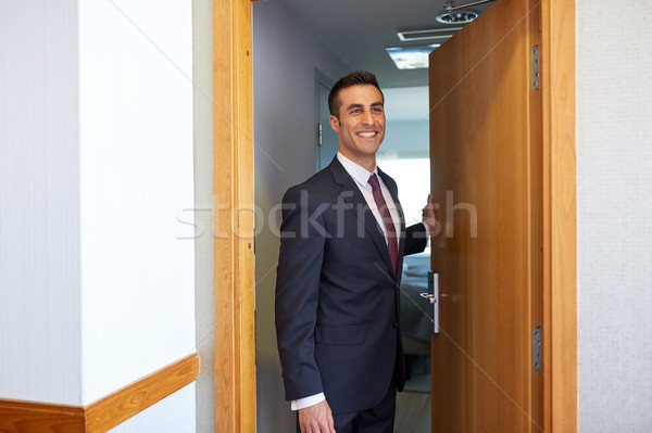 businessman at hotel room or office door Stock photo © dolgachov