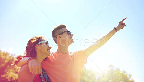 happy couple pointing finger at summer park Stock photo © dolgachov