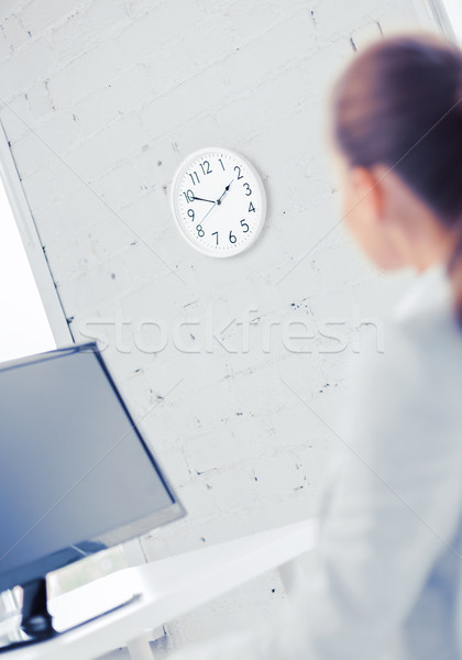 businesswoman looking at wall clock in office Stock photo © dolgachov