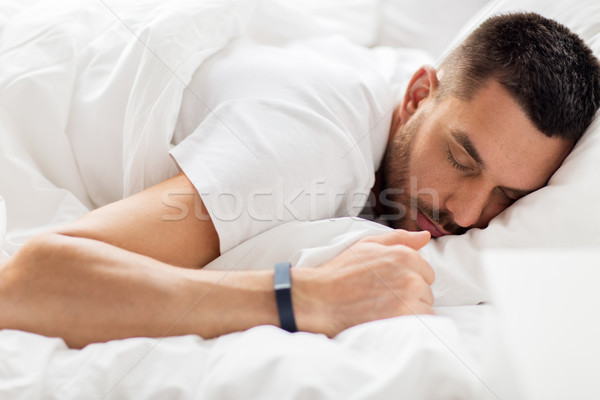 man with smartwatch sleeping in bed Stock photo © dolgachov