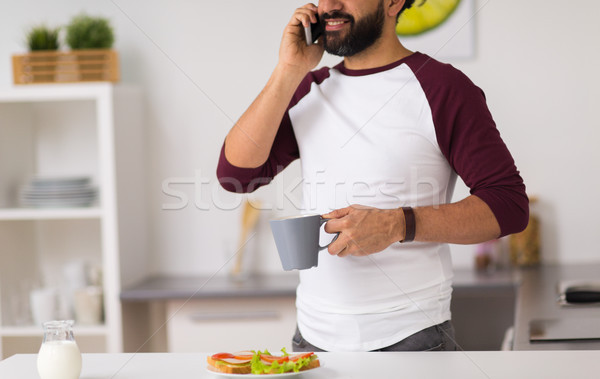man calling on smartphone and eating at home Stock photo © dolgachov
