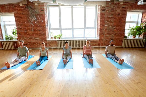group of people doing yoga staff pose at studio Stock photo © dolgachov