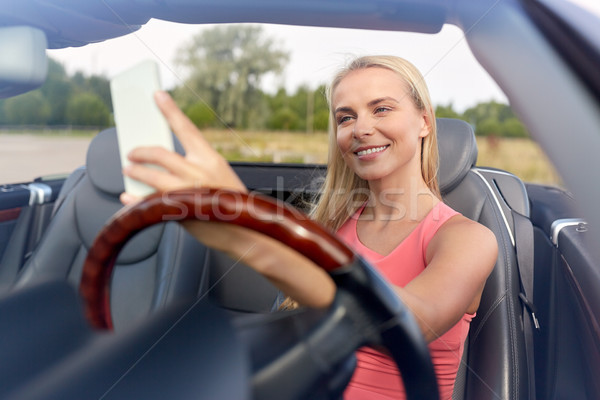 woman in convertible car taking selfie Stock photo © dolgachov