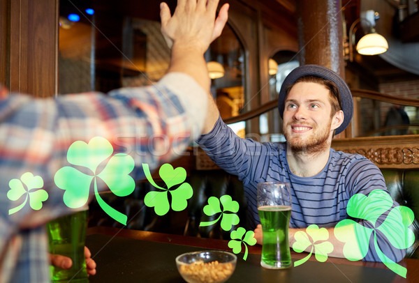 friends with green beer making high five at pub Stock photo © dolgachov