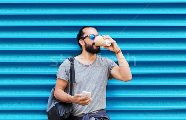 man with smartphone drinking coffee over wall Stock photo © dolgachov