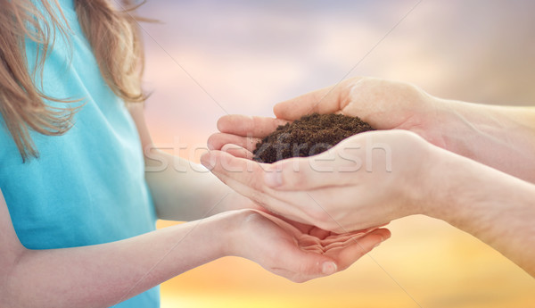 close up of father and daughter hands holding soil Stock photo © dolgachov