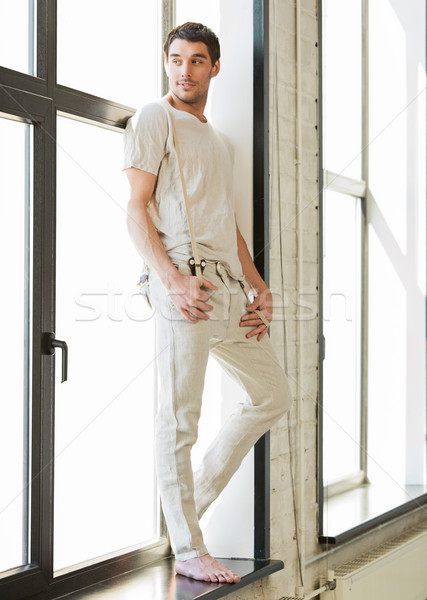 handsome man standing on the windowsill Stock photo © dolgachov