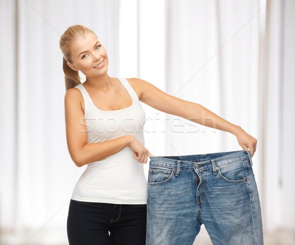 Sportos nő mutat nagy nadrág kép Stock fotó © dolgachov