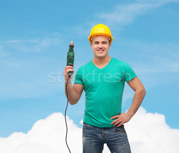 Stock photo: smiling manual worker in helmet with drill machine