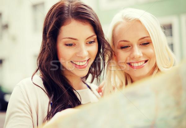 Belle filles regarder touristiques carte ville Photo stock © dolgachov