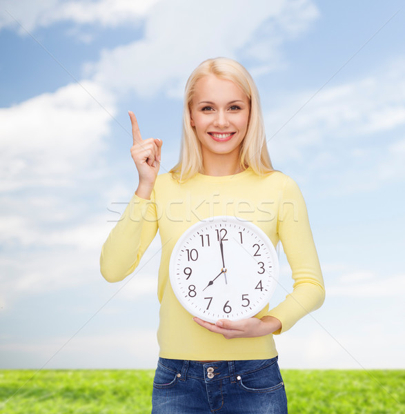 Stock photo: student with wall clock and finger up